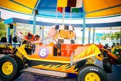 Ragazzo che conduce automobile in parco amusemant fotografie stock