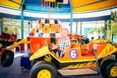 Ragazzo che conduce automobile in parco amusemant immagine stock