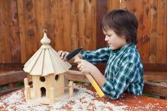 Ragazzo che costruisce un montaggio di casa dell'uccello l'ultimo pezzo del tetto Fotografie Stock Libere da Diritti
