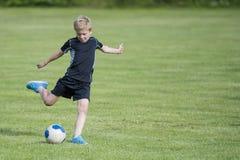 Ragazzo che dà dei calci alla sfera di calcio Fotografia Stock