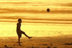 Ragazzo che dà dei calci alla sfera sulla spiaggia Immagini Stock Libere da Diritti