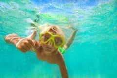Ragazzo che dà pollice su mentre nuotando underwater immagini stock
