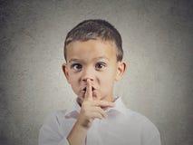 Ragazzo che dispone dito sulle labbra, gesto calmo Immagini Stock