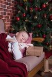 Ragazzo che dorme sul sofà vicino all'albero di Natale con i regali Immagini Stock