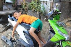 Ragazzo che dorme sulla motocicletta Immagine Stock