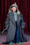 Ragazzo che dura sopra il pagliaccio d'uso graduato Make Up del cappotto Fotografie Stock Libere da Diritti