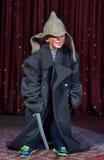 Ragazzo che dura sopra il pagliaccio d'uso graduato Make Up del cappotto Fotografia Stock Libera da Diritti