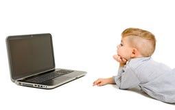 Ragazzo che esamina computer portatile che si trova sul pavimento Fotografie Stock Libere da Diritti