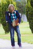 Ragazzo che esamina i libri in sue mani Il bambino va a scuola esterno Fotografie Stock