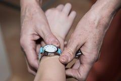 Ragazzo che esamina il suo orologio del bambino del polso immagine stock