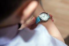 Ragazzo che esamina il suo orologio del bambino del polso fotografia stock