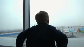 Ragazzo che esamina l'aereo dalla finestra e che imita stock footage