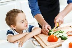 Ragazzo che esamina padre mentre cucinando immagine stock