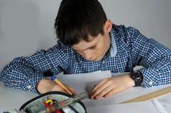 Ragazzo che fa compito di per la matematica Fotografia Stock