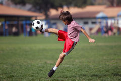 Ragazzo che gioca a calcio nella sosta Fotografia Stock Libera da Diritti