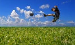Ragazzo che gioca calcio - residuo della potatura meccanica Fotografie Stock