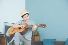 Ragazzo che gioca chitarra in salone a casa Fotografia Stock