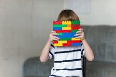 Ragazzo che gioca con i lotti dei blocchi di plastica variopinti dell'interno Fotografie Stock