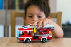 Ragazzo che gioca con il camion dei vigili del fuoco di Lego Fotografia Stock
