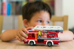 Ragazzo che gioca con il camion dei vigili del fuoco di Lego Immagine Stock Libera da Diritti