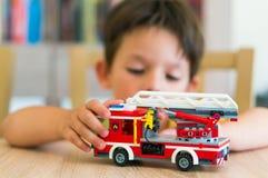 Ragazzo che gioca con il camion dei vigili del fuoco di Lego Fotografie Stock Libere da Diritti