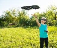 Ragazzo che gioca con il fuco di volo con la macchina fotografica controllata dallo smartphone fotografia stock