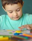 Ragazzo che gioca con la pasta del gioco di colore Fotografia Stock