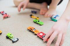 Ragazzo che gioca con la raccolta dell'automobile su tappeto Immagini Stock Libere da Diritti
