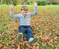 Ragazzo che gioca con le foglie cadute fotografia stock libera da diritti