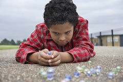 Ragazzo che gioca i marmi sul campo da giuoco Fotografie Stock