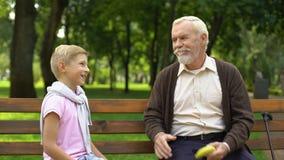 Ragazzo che gioca il gioco di carta di forbici della roccia con il nonno, uomo anziano per perdere e dare banana video d archivio
