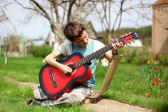 Ragazzo che gioca la chitarra all'aperto Fotografie Stock Libere da Diritti