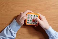 Ragazzo che gioca le cifre di puzzle 15 che si siedono alla tavola Vista superiore Immagine Stock