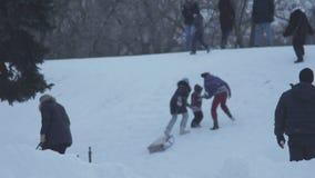 Ragazzo che gioca le palle di neve in parco nevoso nell'inverno mentre sledding dei bambini archivi video