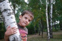 Ragazzo che gioca nella foresta della betulla. fotografie stock