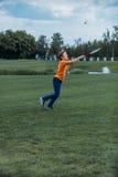 Ragazzo che gioca volano con la racchetta ed il volano, sul campo verde Fotografie Stock