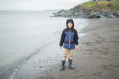 Ragazzo che gode della pioggia e che si diverte fuori sulla spiaggia un gray piovoso Fotografia Stock Libera da Diritti