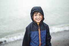 Ragazzo che gode della pioggia e che si diverte fuori sulla spiaggia un gray piovoso Fotografie Stock Libere da Diritti