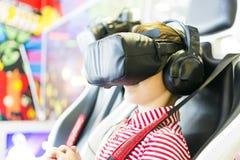 Ragazzo che grida, giochi gogglesplay d'uso di realtà virtuale, collocanti nella sedia 4D sorprendo Bambino che sperimenta aggegg Fotografia Stock