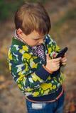 Ragazzo che guarda allo smartphone in vostra mano Fotografie Stock