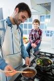 Ragazzo che guarda mentre padre che cucina alimento Immagine Stock