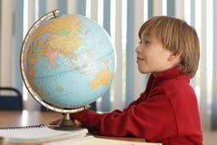 Ragazzo che guarda un globo nella classe di geografia Fotografie Stock Libere da Diritti