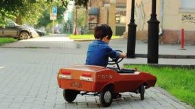 Ragazzo che guida un'automobile del giocattolo stock footage