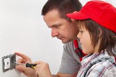 Ragazzo che impara come riparare un dispositivo elettrico della parete immagini stock libere da diritti
