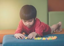 Ragazzo che impara giocare il giocattolo duro di puzzle immagine stock