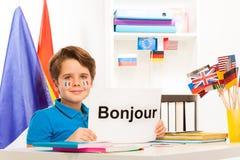 Ragazzo che impara seduta francese allo scrittorio in aula Fotografia Stock