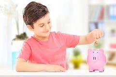 Ragazzo che inserisce le monete in un porcellino salvadanaio Fotografia Stock