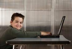 Ragazzo che lavora ad un computer portatile Fotografia Stock
