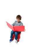 Ragazzo che legge un grande libro rosso Immagine Stock Libera da Diritti