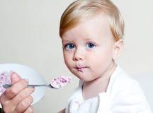 Ragazzo che mangia alimenti per bambini con il cucchiaio Fotografie Stock Libere da Diritti